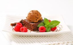 Chocolate Brownie with ice cream and raspberries. Chocolate brownie with ice cream and fresh raspberries Stock Image