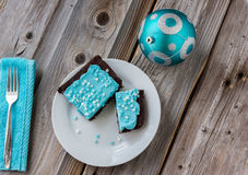 Chocolate brownie on plate with blue icing on wood surface Stock Images