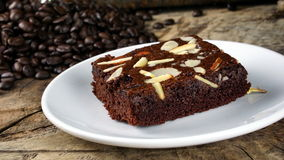 Chocolate Brownie. Put on a wood table with dark roasted coffee beans Royalty Free Stock Photos