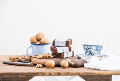 Chocolate brownie slices wrapped in paper and tired with rope, porcelain tea cup, enamel mug of walnuts on rustic wooden Stock Photo