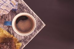 Chocolate brownie sprinkled with cocoa and coconut in the background with a coffee mug on the corner of a table near a royalty free stock images