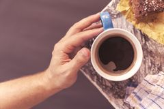 Chocolate brownie sprinkled with cocoa and coconut in the background with men`s hand takes a coffee mug on the corner of stock photos