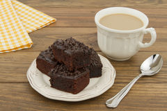 Chocolate brownie and a white coffee cup Stock Photos