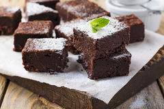 Chocolate brownies with powdered sugar and cherries on a dark wooden background. Selective focus royalty free stock photography