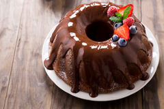 Chocolate bundt cake with berries. Chocolate bundt cake with melted chocolate and frozen berries Stock Image