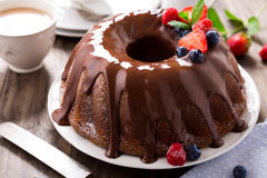 Chocolate bundt cake with berries. Chocolate bundt cake with melted chocolate and frozen berries Royalty Free Stock Image