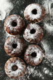 Chocolate bundt cakes with icing sugar on black background Royalty Free Stock Images