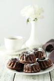 Chocolate bundt cakes on plate on white wooden background Stock Photos