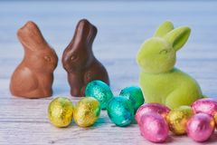 Chocolate bunnies and chocolate eggs and in front a green bunny royalty free stock photos