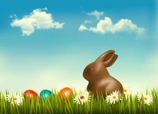 Chocolate bunny with easter eggs in grass. Stock Photos