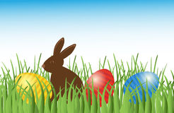 Chocolate bunny with easter eggs in grass. Vector. Royalty Free Stock Images