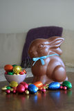 Chocolate bunny with Easter eggs on table. Chocolate bunny rabbit with blue neck tie and Easter eggs on table Stock Photo