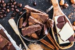 Chocolate, cacao y especias adentro en una tabla Imágenes de archivo libres de regalías