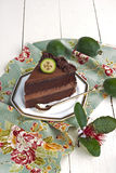 Chocolate cake. Piece of rich chocolate cake with chocolate mousse decorated with feijoas. French country style with rustic wooden table and old blue napkin stock image