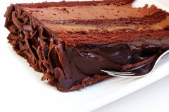 Chocolate Cake. A slice of gooey chocolate mud cake on a white plate, with silver cake fork royalty free stock image