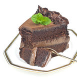 Chocolate cake. Piece of rich chocolate cake with chocolate mousse decorated with fresh mint leaves isolated on white royalty free stock image
