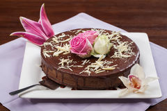 Chocolate cake. A big chocolate cake with sauce and some flowers Stock Photography