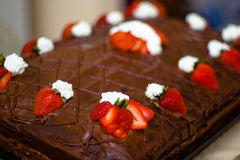 Chocolate cake. A closeup of a chocolate cake, decorated with strawberries and cream stock image