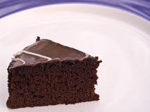 Chocolate Cake. A slice of iced chocolate cake on a white plate stock image