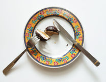 Chocolate cake. The cut chocolate cake, knife and fork, lie on a dish Stock Photo
