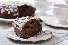 Chocolate cake with almond. Chocolate cake on vintage plate with cup of tea Stock Photos