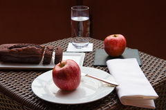 Chocolate cake and apple. Breakfast on the terrace wicker table with chocolate cake and two red apples Stock Photo