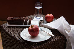 Chocolate cake and apple. Breakfast on the terrace wicker table with chocolate cake and two red apples Stock Photography