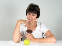 Chocolate cake or apple. Woman making decision about diet, healt Royalty Free Stock Photos