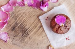 Chocolate cake on a baking paper served with  rose petals on a wooden sevice plate, above vanta stock photo