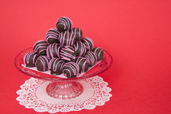 Chocolate cake balls stripped  pink candy melts stacked on plate. Hocolate cake balls stripped with pink candy melts stacked pyramid pattern on a pink glass Royalty Free Stock Photo