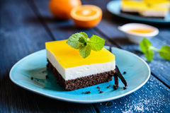 Chocolate cake bars with mascarpone layer and orange jelly topping. Delicious chocolate cake bars with mascarpone layer and orange jelly topping royalty free stock images