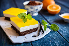 Chocolate cake bars with mascarpone layer and orange jelly topping. Delicious chocolate cake bars with mascarpone layer and orange jelly topping stock photo