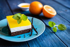 Chocolate cake bars with mascarpone layer and orange jelly topping. Delicious chocolate cake bars with mascarpone layer and orange jelly topping royalty free stock photos