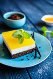 Chocolate cake bars with mascarpone layer and orange jelly topping. Delicious chocolate cake bars with mascarpone layer and orange jelly topping stock photography