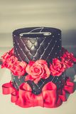 Chocolate cake. Chocolate birthday cake with red roses, big red ribbon and cyrillic letter D on the top, copy space Stock Image