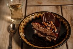 Chocolate cake on a black plate with tea on a wooden background. stock image