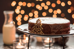 Chocolate cake with blurry christmas lights. Still life of chocolate cake and a bottle of milk with blurry christmas lights Royalty Free Stock Photo