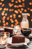 Chocolate cake with blurry christmas lights. Still life of chocolate cake cup of coffee and bottle of milk with blurry christmas lights Royalty Free Stock Image