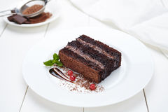 Chocolate cake brownie with cocoa cream and berry sauce Royalty Free Stock Photos