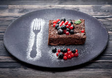 Chocolate cake brownie with summer berries. On dark background Royalty Free Stock Photos