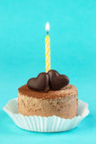 Chocolate cake with a candle on a bright background. Party Stock Image