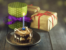 Chocolate cake with a candle and gifts.Happy Birthday, card. Holidays greeting card. Stock Photo