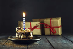 Chocolate cake with a candle and gifts. Happy Birthday, card. Holidays greeting card. royalty free stock photography
