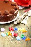 Chocolate cake and candles in the form of letters. Royalty Free Stock Image