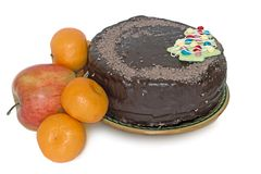 Chocolate cake on a ceramic platter and fruit on a white backgro Royalty Free Stock Photos