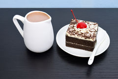 Chocolate cake with cherry and milk jug. On black wooden table Royalty Free Stock Image