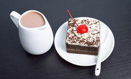 Chocolate cake with cherry and milk jug. On black wooden table Stock Photos