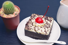 Chocolate cake with cherry and milk jug, cactus. On black wooden table Stock Image