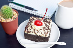 Chocolate cake with cherry and milk jug, cactus, notebook. On black wooden table Stock Photography