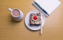 Chocolate cake with cherry and milk jug, notebook, cactus. On wooden table Royalty Free Stock Images